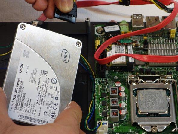 Ziehen Sie den zweiten Stecker der SSD Festplatte aus, indem Sie auf die Entriegelungsfeder drücken.