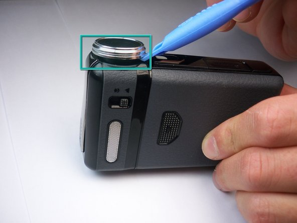 Break the glue that attaches the lens cover to the camcorder by sliding the plastic prying tool underneath the circumference of the part.