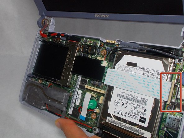 The ribbon cable covering the hard drive and connecting to the motherboard is  held in using zero insertion force (ZIF) connector.