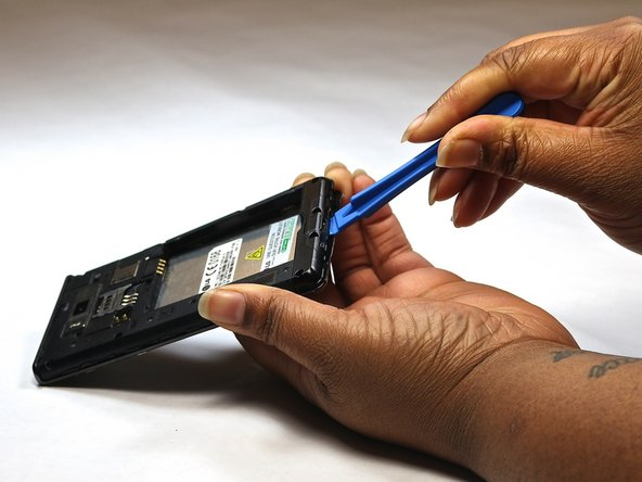 Insert a plastic opening tool between the seams of the device and apply some pressure to lift off the cover.