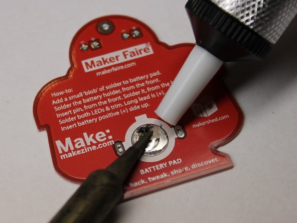 Depress the plunger in the desoldering tool until it clicks.