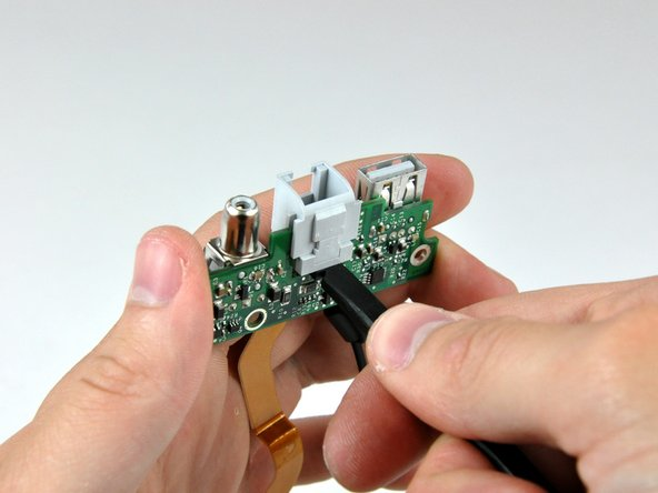 Use the flat end of a spudger to continue removing the RJ-11 board away from the DC-In board.