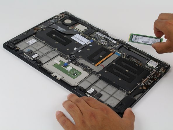 Use the plastic opening tool to remove the hard drive/SSD.