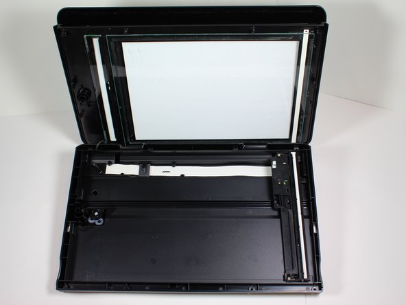 Detach the scanner glass by slowly moving the glass side away from the back side of the cartridge access door.