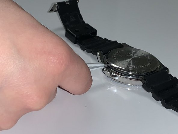 Remove the back cover of the watch with  tweezers.