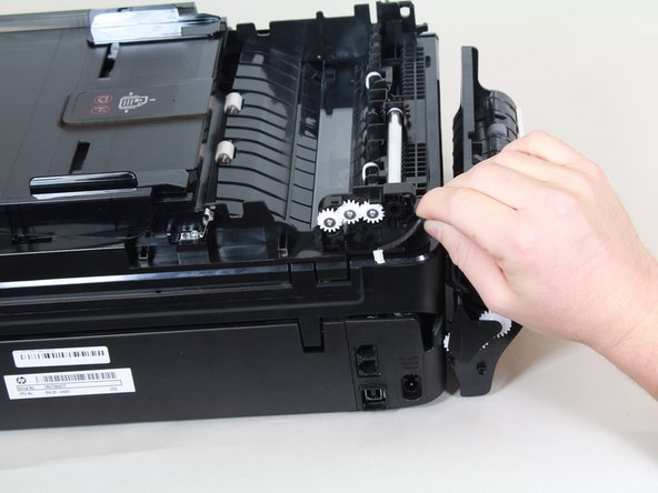 Remove the wire cover and pull the wire away from the printer. The fax feeder head is now free to be separated from the printer.