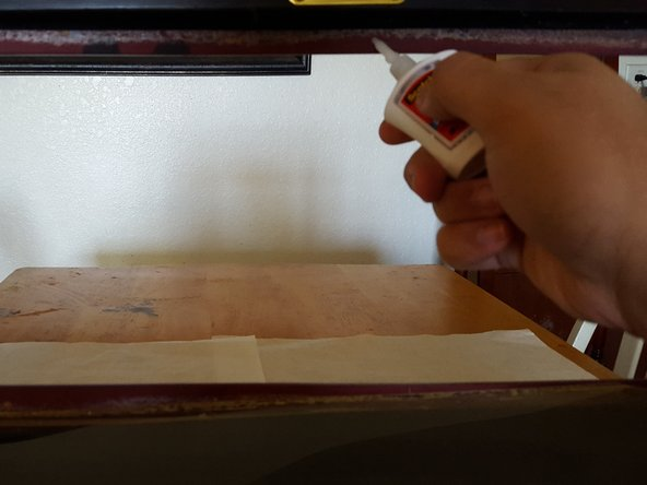 Apply a thin, solid line of a strong adhesive, such as Gorilla Glue, to the entire inner border of the display case where the glass attaches.