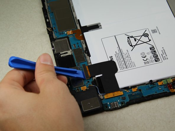 Gently place the larger plastic opening tool under the ZIF connector on the bottom left of the device.