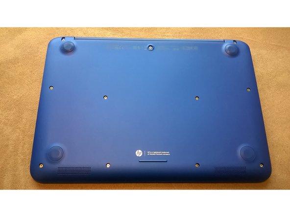 Drehe das Laptop um. Auf der Rückseite befinden sich vier Gummifüsschen, die entfernt werden müssen, um an die Schrauben darunter zu kommen. Entferne zuerst, wie auf dem Bild gezeigt, das Gummifüsschen in der Mitte.