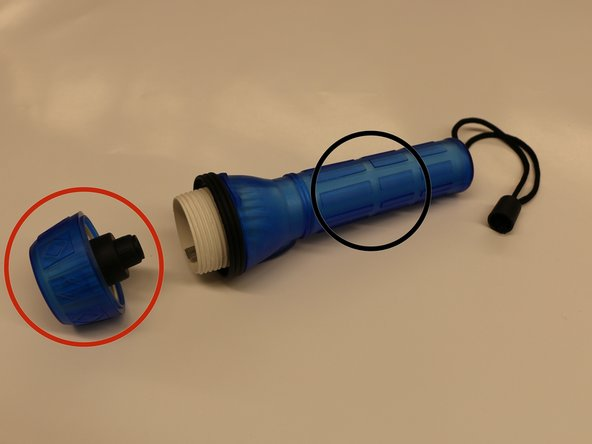 Remove light mechanism from body containing battery. Twist light bulb (red circle) counterclockwise while holding base of flashlight (black circle).