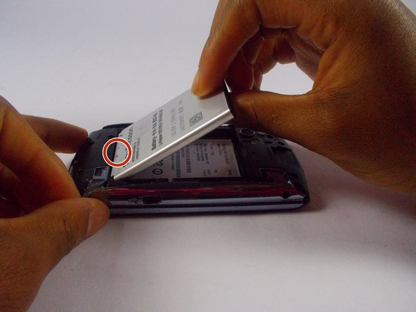 Once the old battery id removed, slide the new battery, with the positive/negative indicator facing up, in so that the contacts of the battery make contact with the contacts of the phone.