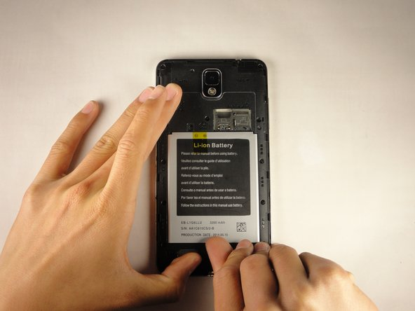 Remove the battery by placing your thumb in the slot, pushing the battery up and pulling it out.