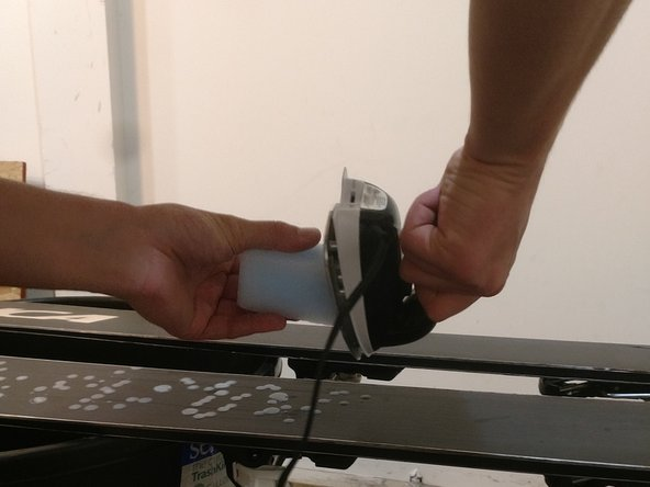 Spread wax across the base of the ski with an edge to edge motion.  While doing this hold the iron perpendicular to the base and press the wax into the iron.