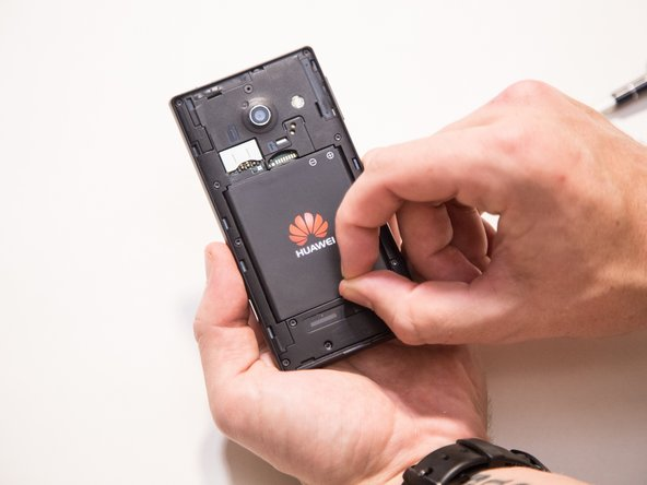 Image 2/3: Lift the battery out of the phone with your fingers by pressing forward and lifting upward.