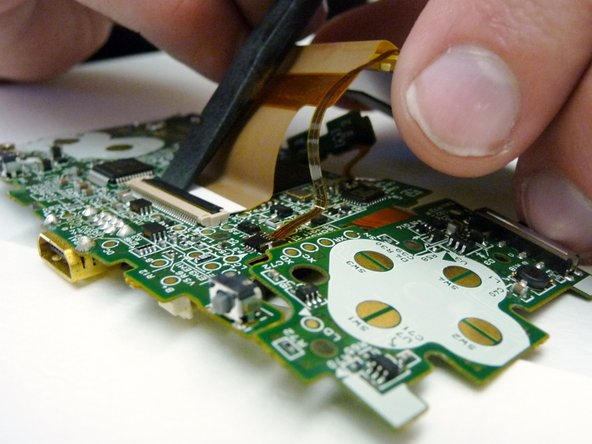 Image 3/3: Use a plastic spudger to disconnect the LCD's ZIF connector.
