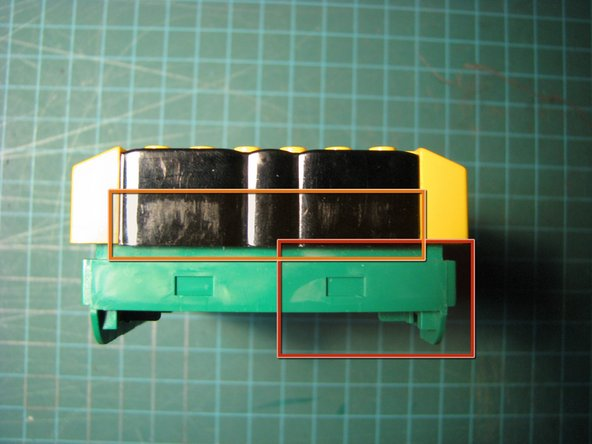 Image 1/2: Pull the right side of the battery compartment away from the top case. The left side will be held in place by the battery clip.
