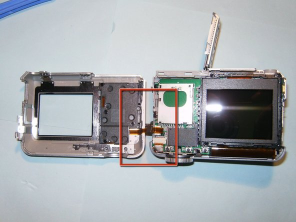 Do not try to totally separate the back case. It is still connected by a ribbon cable. Set the connected cases side by side.
