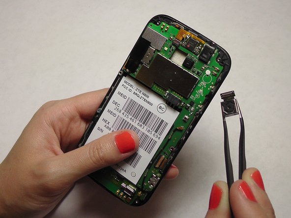 Use the tweezers to grip the back facing camera. Gently pull until the camera is completely removed from the motherboard.