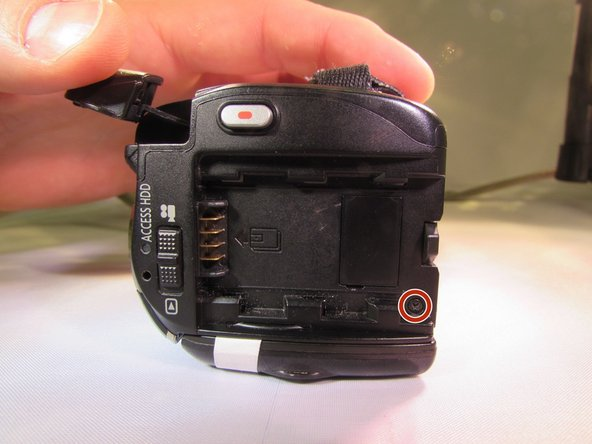 Remove the black 4 mm screw from the back of the camcorder underneath where the battery would have been.