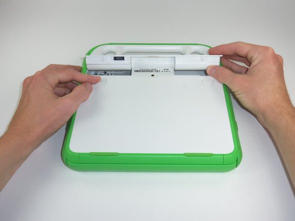 Image 1/1: The right tab will stay in place, but the left tab must be held in position while you remove the battery.