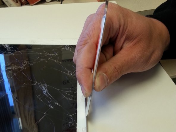 Once the screen is fairly heated up take your prying tool and find the little crack between the frame of the iPad and the iPad's screen. Once you've located the crack place your tool between the crack and press down to cut through the glue.