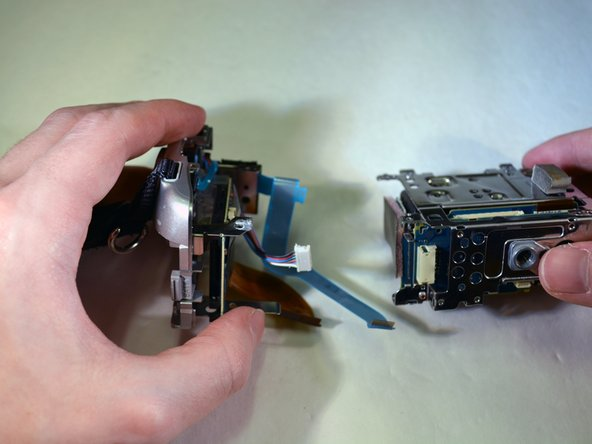 Image 3/3: To separate the two pieces of the device, apply force downwards on the right piece to separate them.