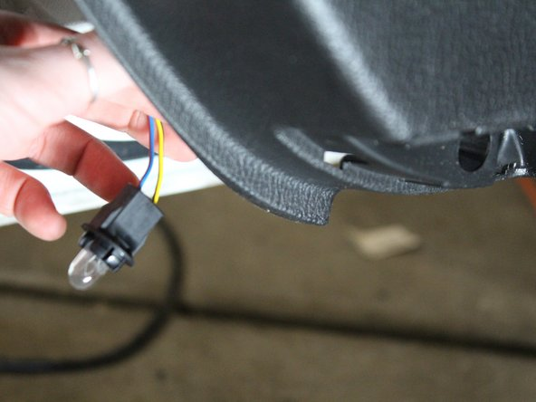 Use a flathead screwdriver to press the clip holding the light from the back of the door and pull the lightbulb out.