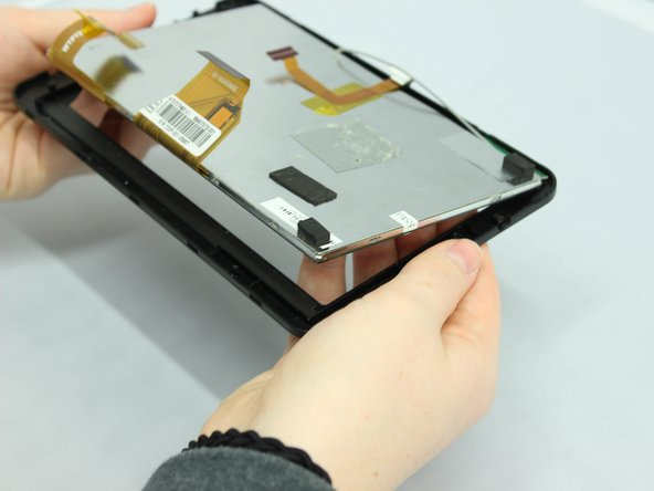 Image 1/1: Using your fingers, push upward from below on the screen until the screen and display unit pop out of the black plastic frame.