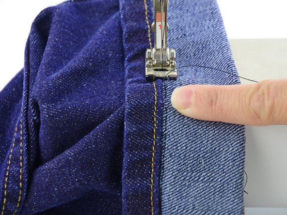 Image 1/1: In this photo we've sewn slightly off of the edge of the hem for visibility. When you sew your jeans, you will want to sew as close to that edge as possible.