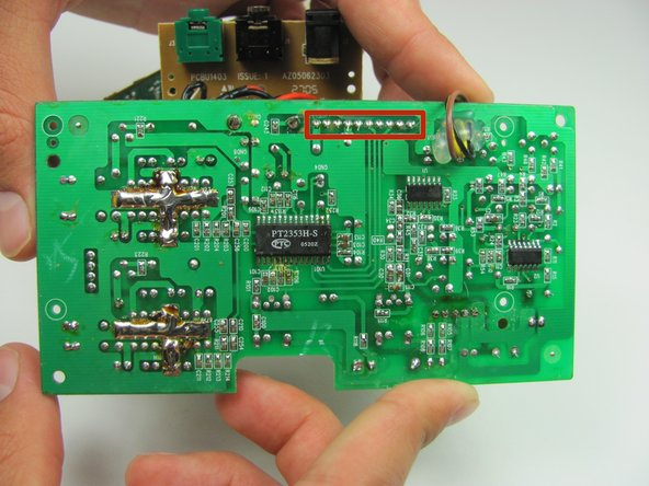 Image 3/3: Turn over the motherboard and remove the solder connecting the wide, flat, grey wire.