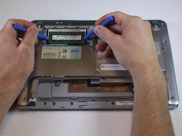 Using two plastic opening tools (or your fingers) pull two tabs holding RAM outwards.