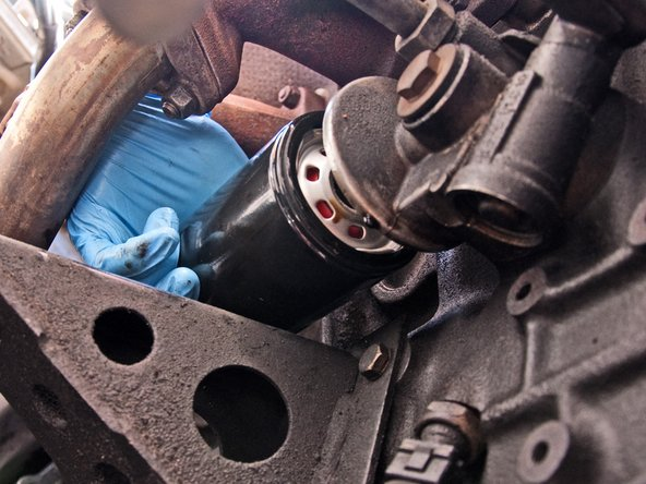 Without getting any dirt or contaminants on the seal you just oiled, maneuver your new oil filter into position.