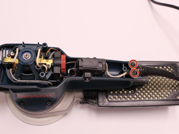 Image 1/3: Lift the cable clip and cord from motor housing.