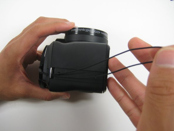 After successfully placing the string through the metal slab, pull the string all the way to the right which will leave enough room to tie the lens cover to the camera.