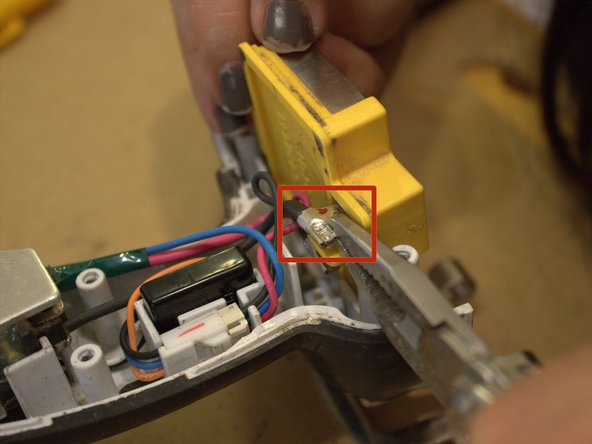 Using a pair of thin-nose pliers, carefully remove the blade connectors from the positive and negative leads on the battery terminal.