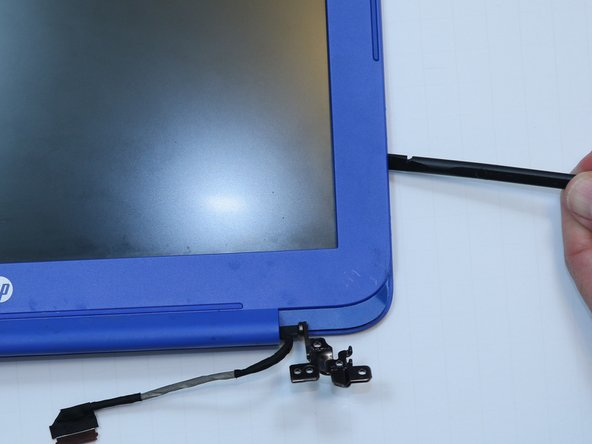 Use a plastic spudger to pry the bezel away from the screen.