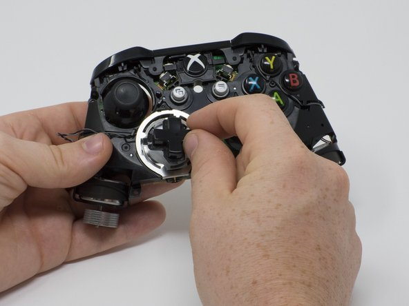 Turn the device over and remove the directional pad by gently pulling it away from the controller.