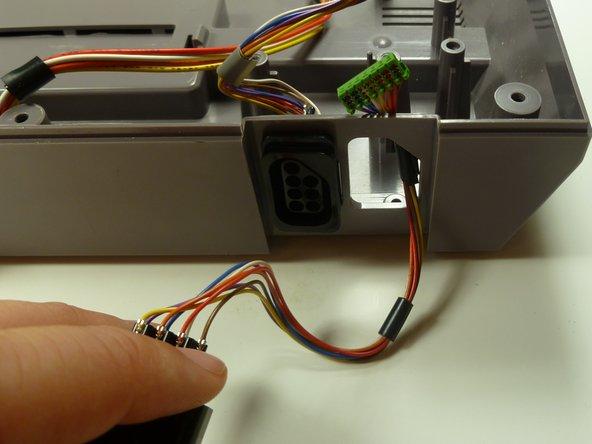 Ziehe den Anschluss mit der Hand gerade heraus, im Gehäuse der NES bleibt eine Öffnung zurück.