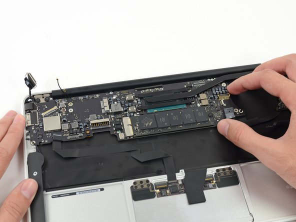Gently lift the logic board assembly from the heat sink end and pull it away from the port side of the case to remove it from the Air.