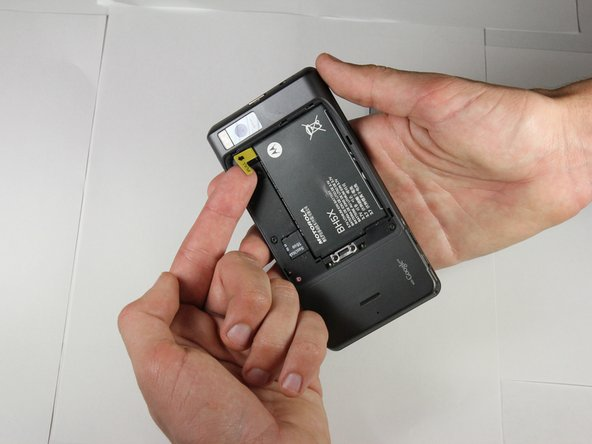 Find the yellow pull tab located in the upper left corner.  Pull the tab until the battery dislodges. Grab the battery by the raised edge, and remove it from the case.