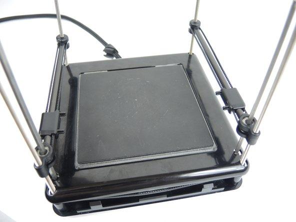 Retire la cubierta de la cama de impresión y ubique los cuatro tornillos que sujetan la cama de impresión a la base de la unidad. Retire los cuatro tornillos de 9,5 mm con la cabeza hexagonal de 3,5 del kit de brocas.