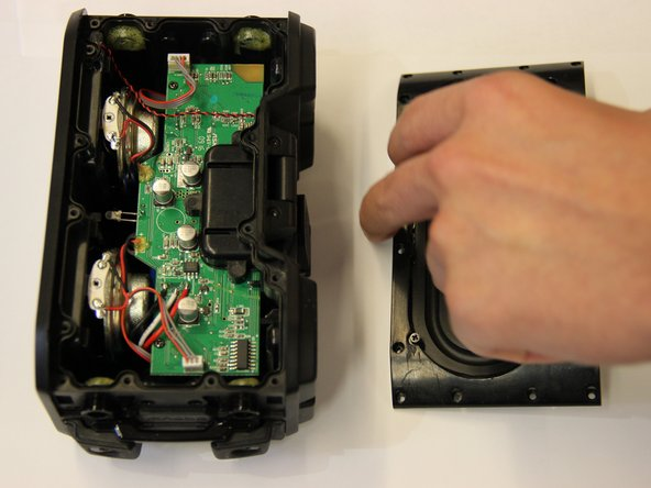 Carefully lift away the broken sub-woofer plate of the device. Replace with functioning sub-woofer plate.