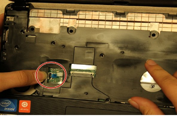Before the baseboard can be fully removed from the laptop, you need to detach the small blue tab attached to the motherboard.