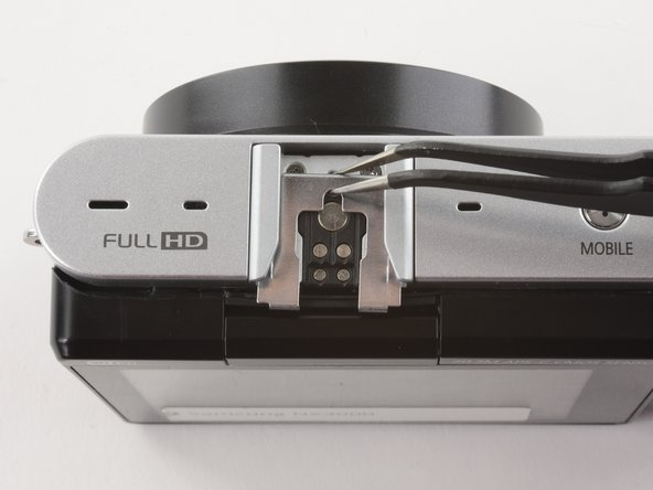 Use tweezers to remove the metal shield from the external flash mount.