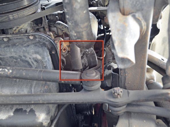 Image 1/2: Slide the oil drain pan below the oil filter so that it will catch any oil that drips down when the oil filter is removed.