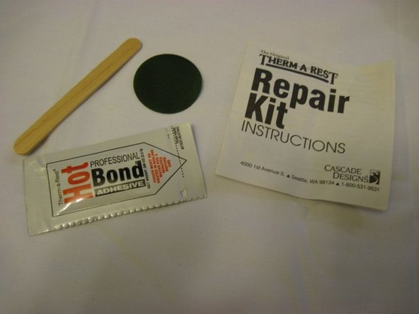 Obtain a Therm-a-Rest repair kit including a packet of HotBond Adhesive, patch, and wood stick or similar.