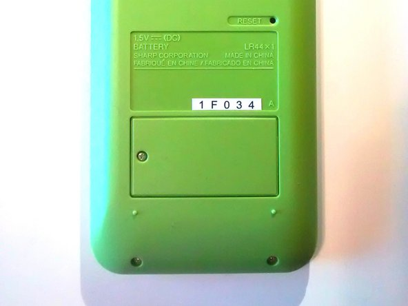 Image 3/3: Flip the device over so the green backing and battery door face up.