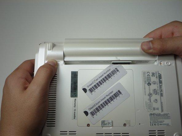 Faites glisser la batterie tout en maintenant le loquet de verrouillage gauche en position déverrouillée.