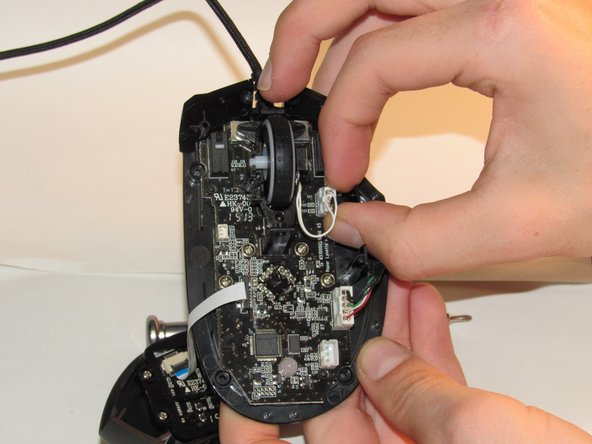 Unplug the cord that connects the scroll wheel to the circuit board.