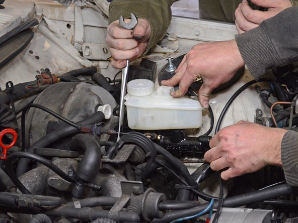 Image 1/2: Remove the brake master cylinder, taking care not to damage or bend the brake lines.